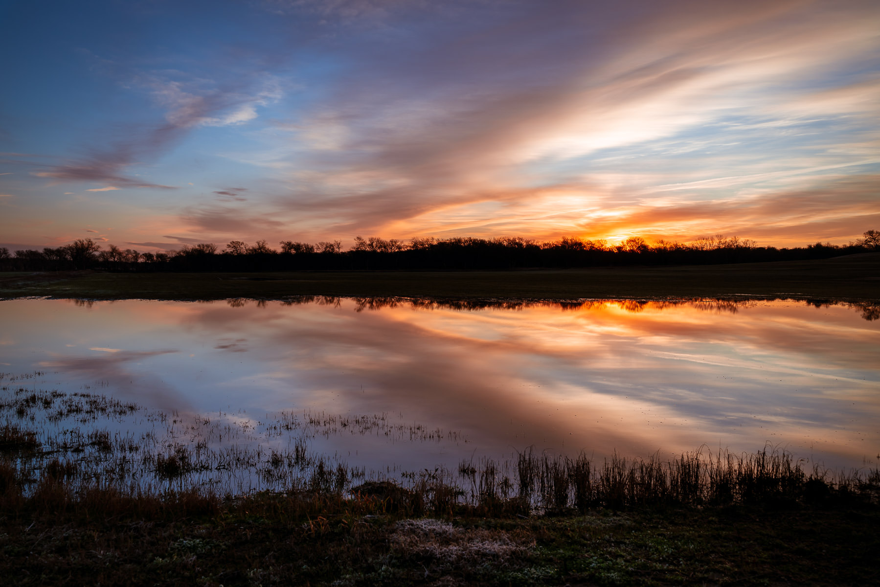The sun rises on a pond at Texas' Hagerman National Wildlife Refuge.