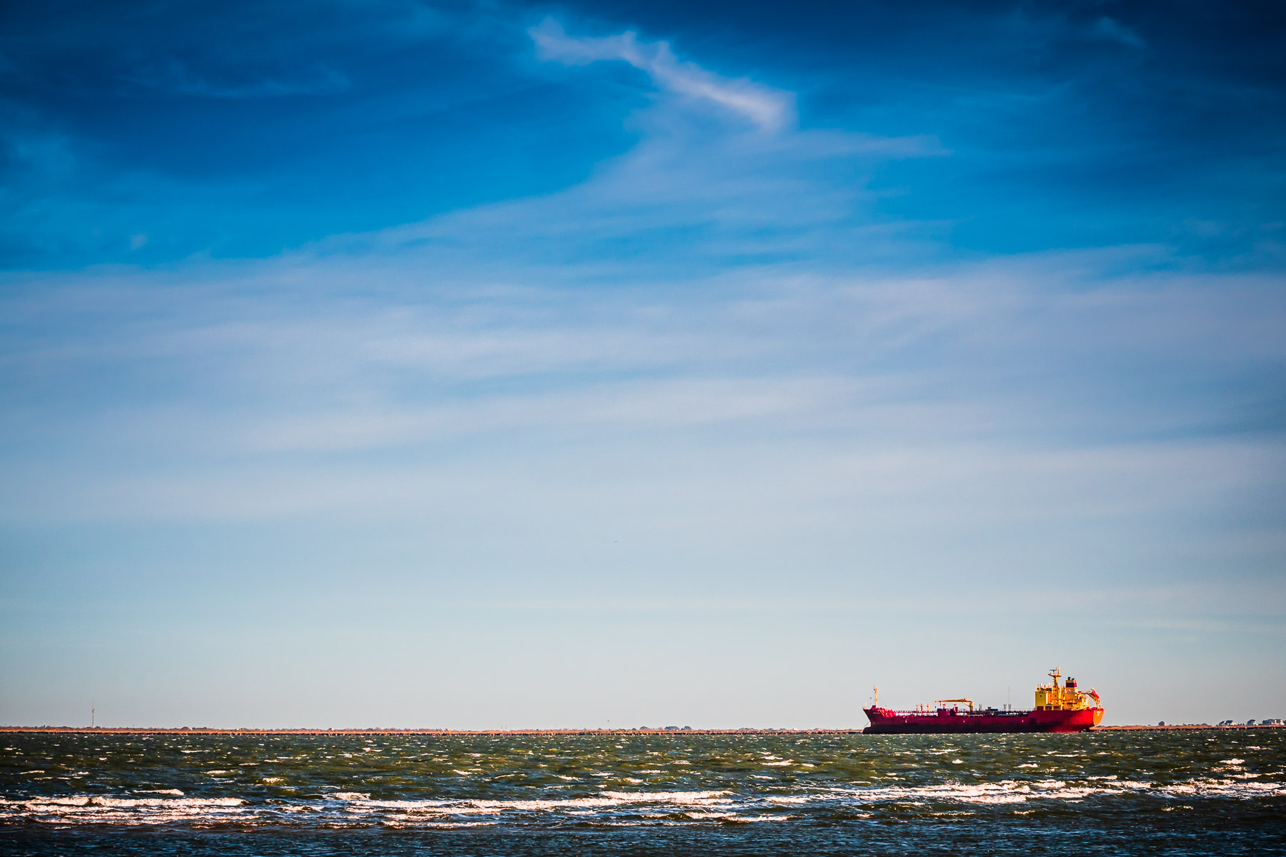 The chemical tanker Cape Daly transits Bolivar Roads off the eastern tip of Galveston Island, Texas.