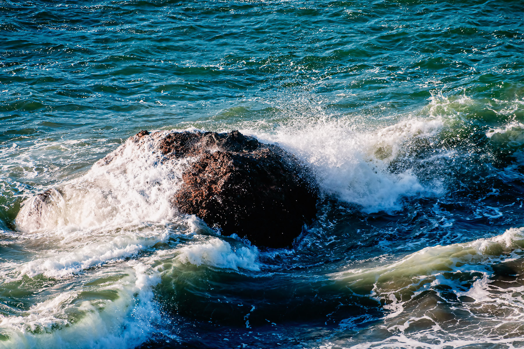 Waves crash over a rock along the Pacific Ocean shoreline at Lands End, San Francisco.