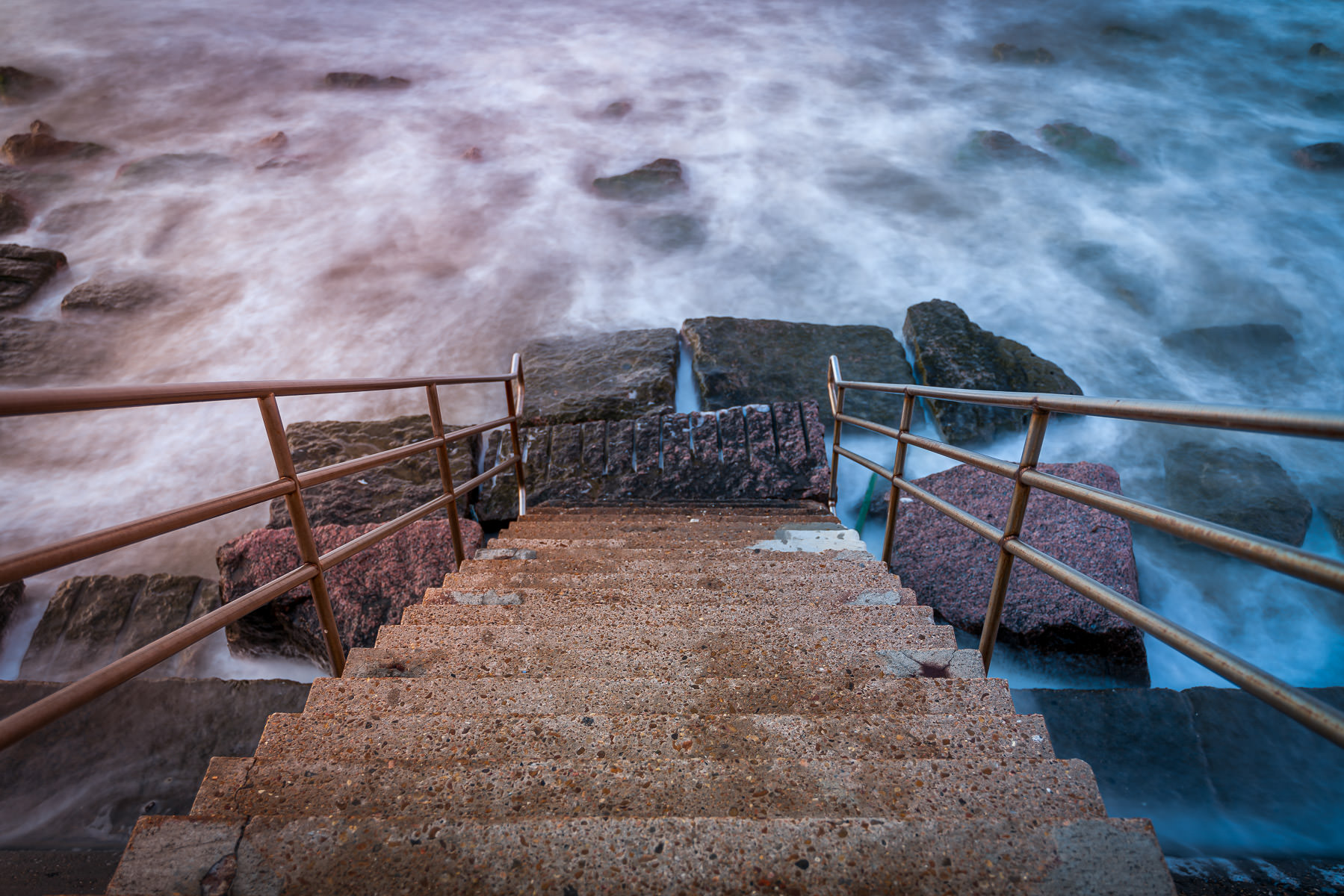 Stairs on the Galveston, Texas, Seawall lead to the morning surf.