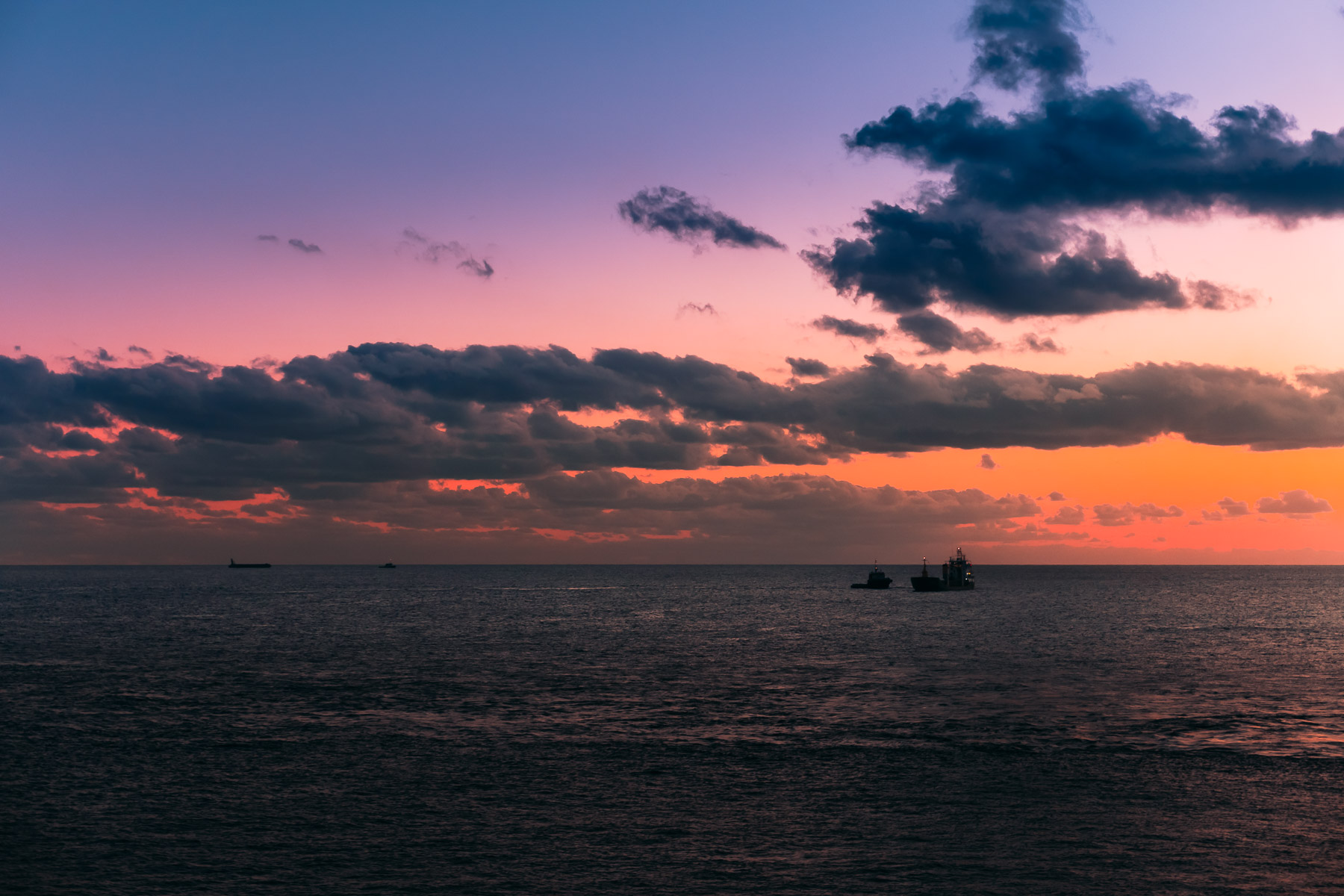 The sun sets on boats off the shore of Grand Cayman.