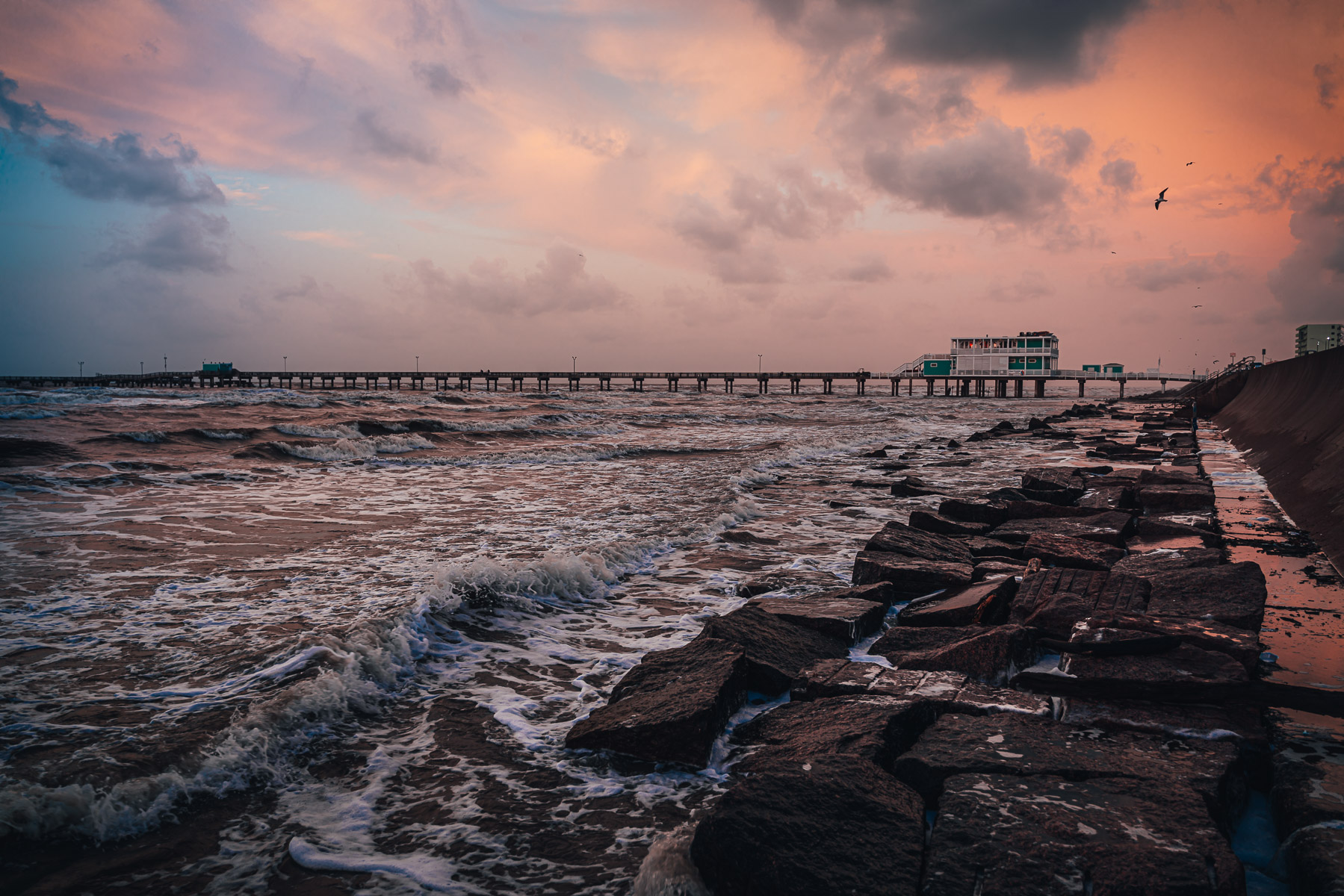 The Galveston Fishing Pier reaches into the morning surf of the Gulf of Mexico.