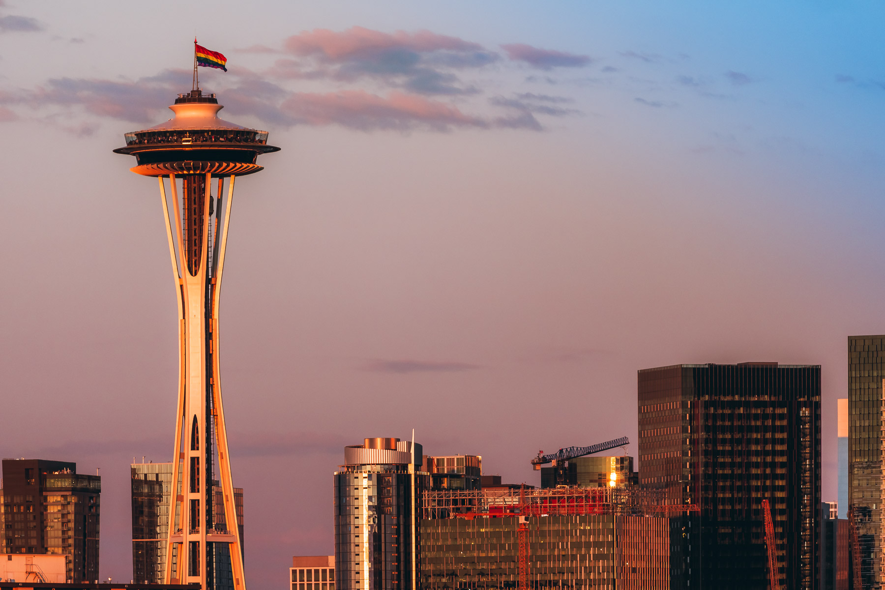 The evening sun lights the Seattle Space Needle, adorned with a LGBT Pride flag for Pride Month.