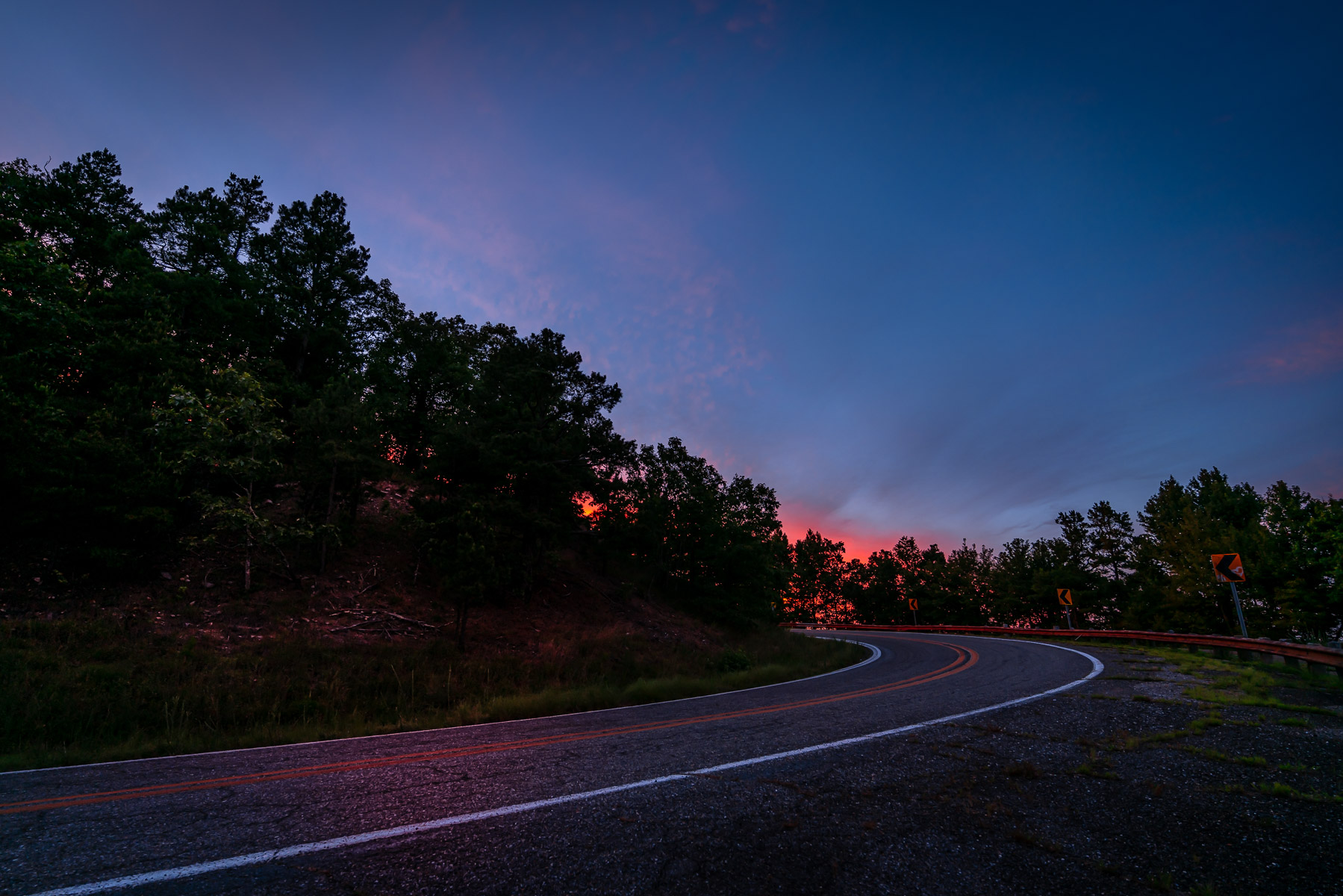 The Talimena National Scenic Byway twists through the Ouachita National Forest towards the setting sun near Mena, Arkansas.