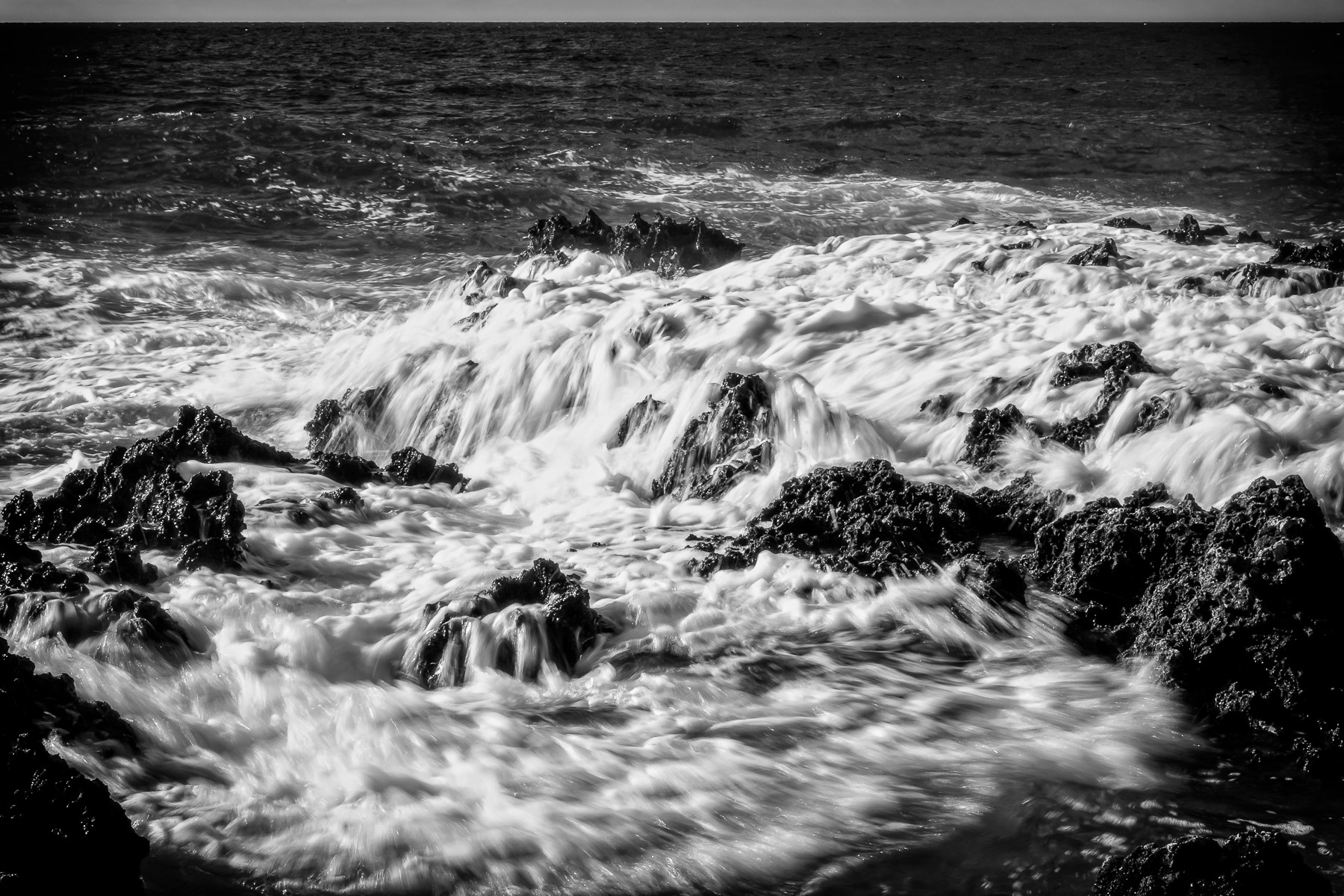 Caribbean Sea waves froth over rocks at Turtle Reef at West Bay, Grand Cayman.