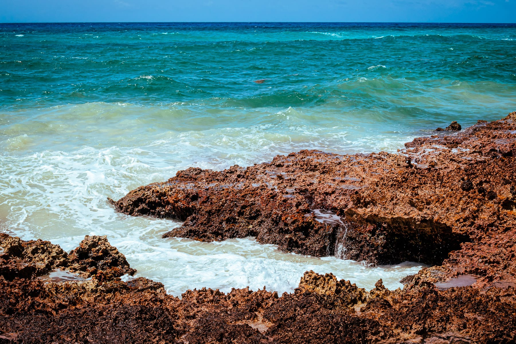 Jagged rocks jut into the sea at Punta Morena, Cozumel, Mexico.
