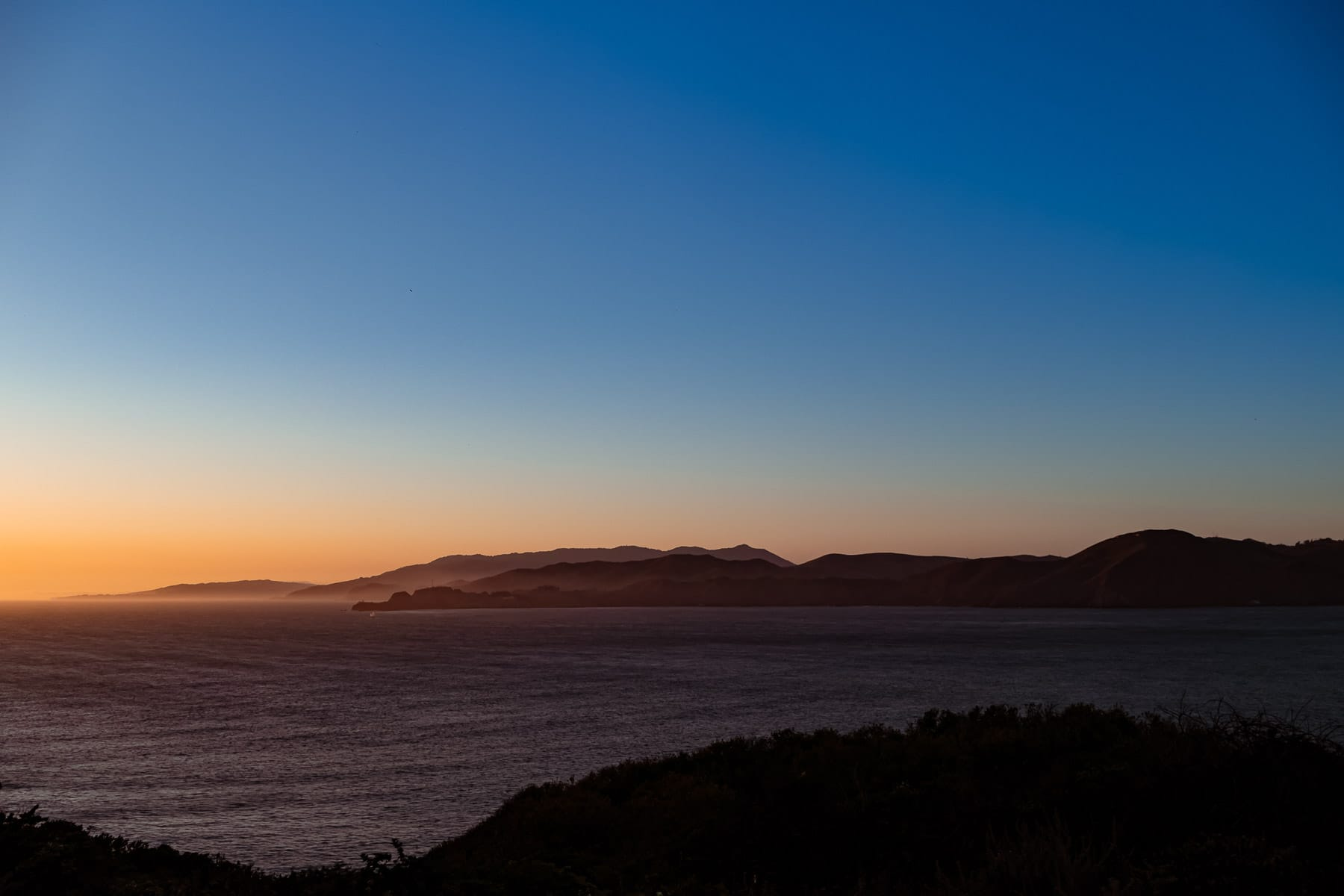 The sun sets on the Pacific Ocean and Point Bonita, California, as seen from the Lands End, San Francisco.