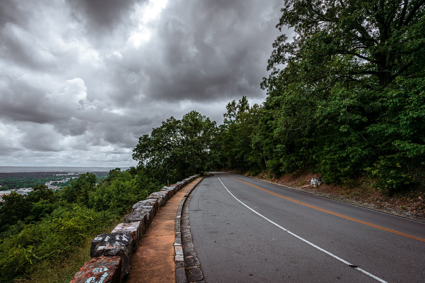 A road curves around a mountaintop overlooking Hot Springs, Arkansas.