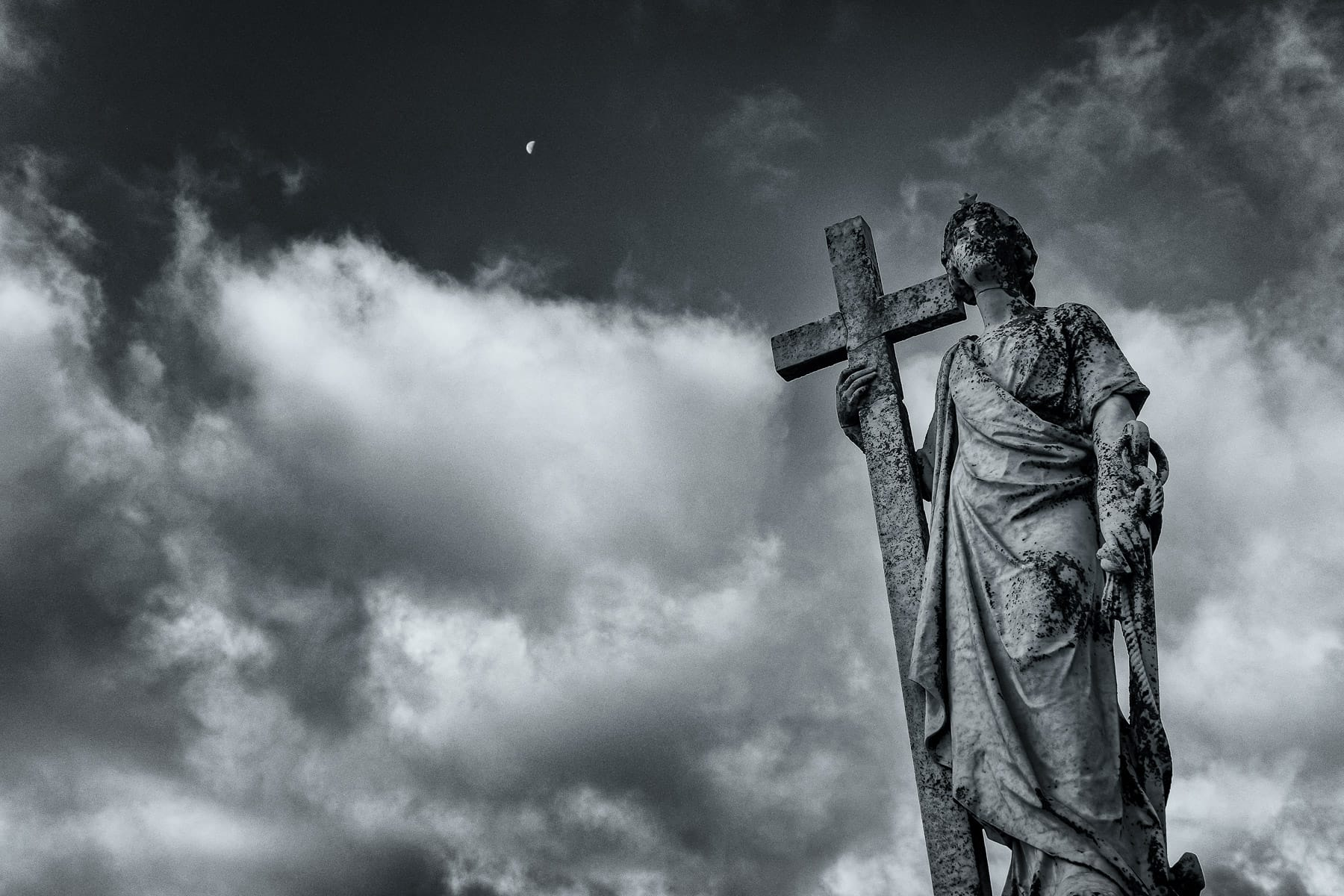 A statue atop a grave at a Galveston, Texas, cemetery appears to watch the sky.
