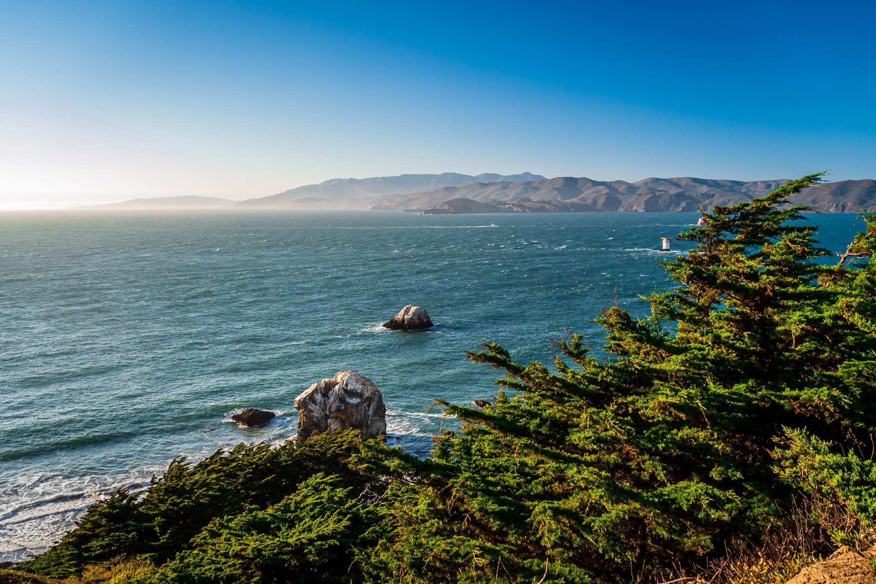 The Pacific Ocean narrows into the Golden Gate at the headlands of the Marin Peninsula and San Francisco Peninsula as seen from Lands End.