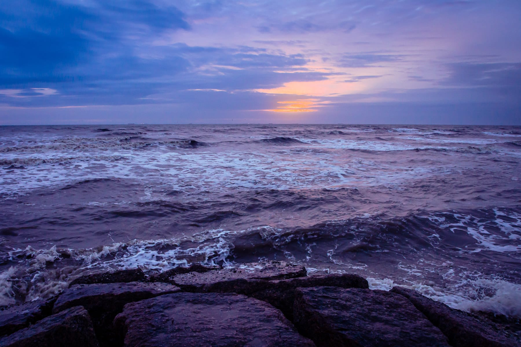 The sun rises on the Gulf of Mexico, as seen from a granite groyne along the Galveston, Texas, beach.