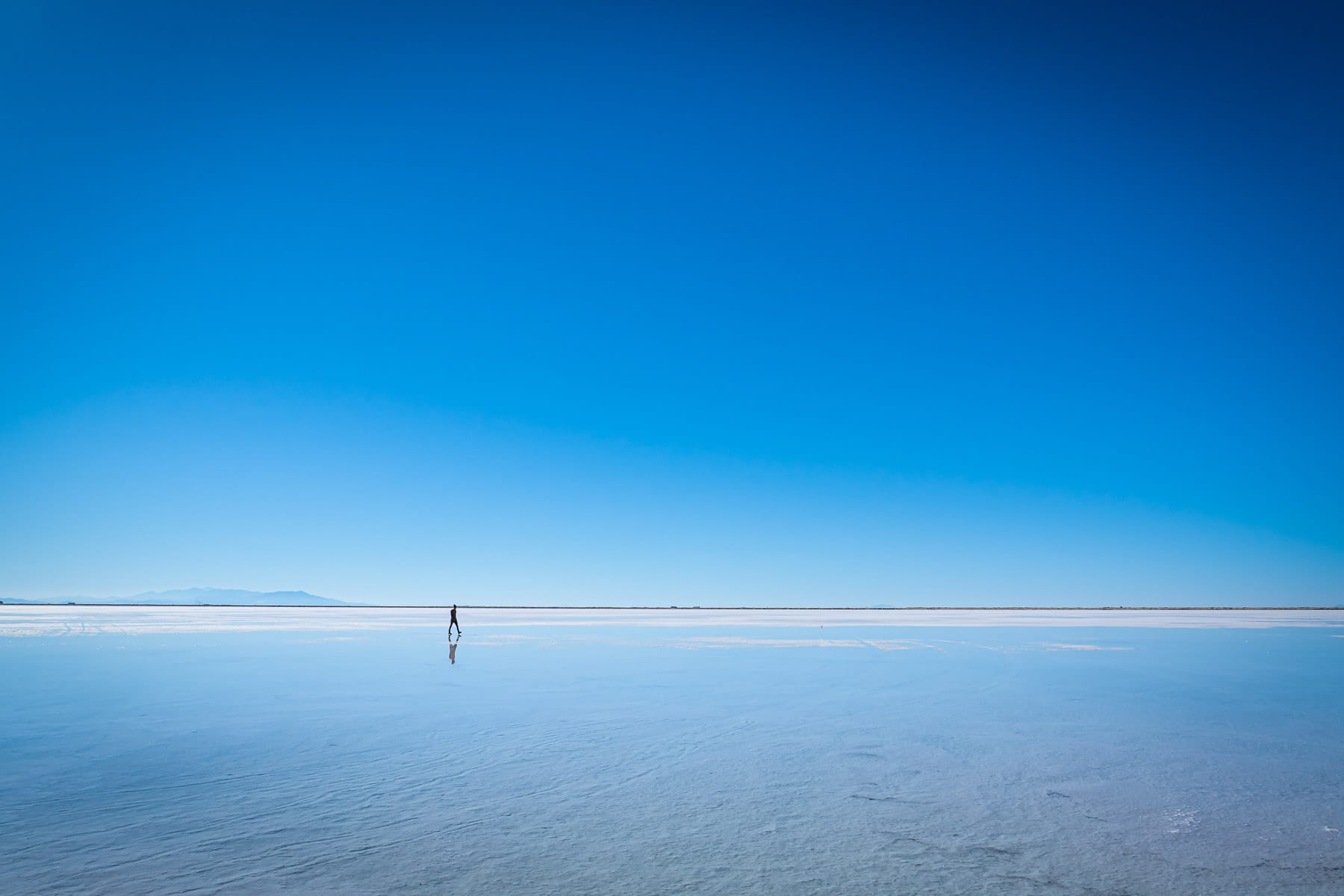 A lone figure walks among the other-worldly, seemingly-endless expanse of the Bonneville Salt Flats, Utah.
