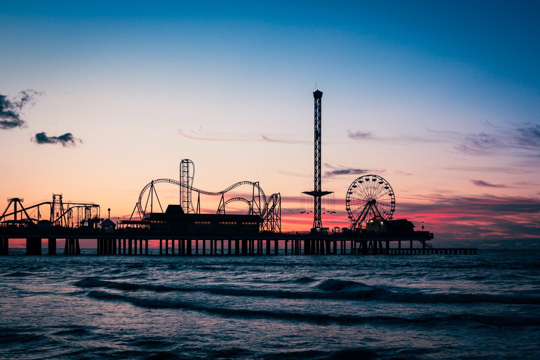 The Galveston Island Historic Pleasure Pier is silhouetted by the sunrise over the Gulf of Mexico.