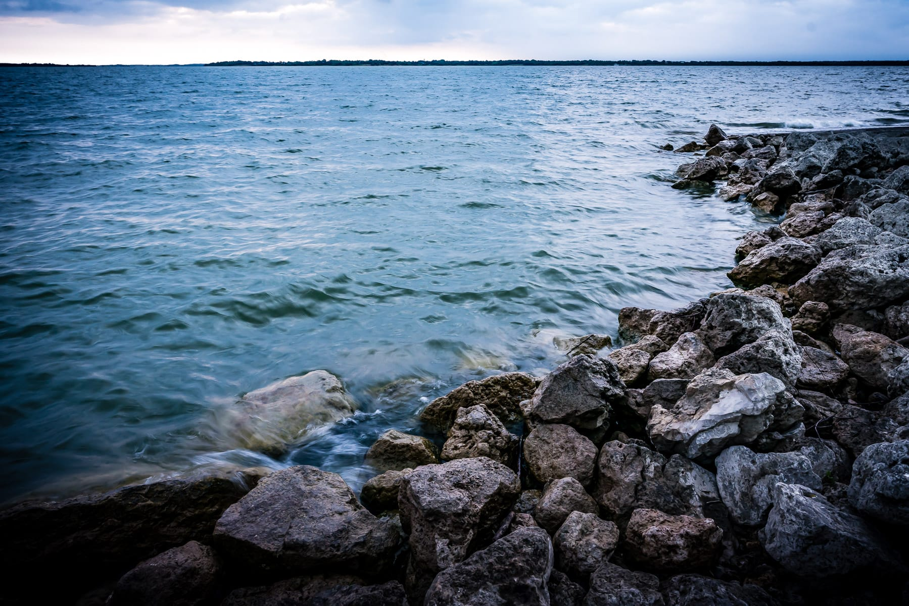 Waves lap at the rocky shore of North Texas' Lake Lavon.
