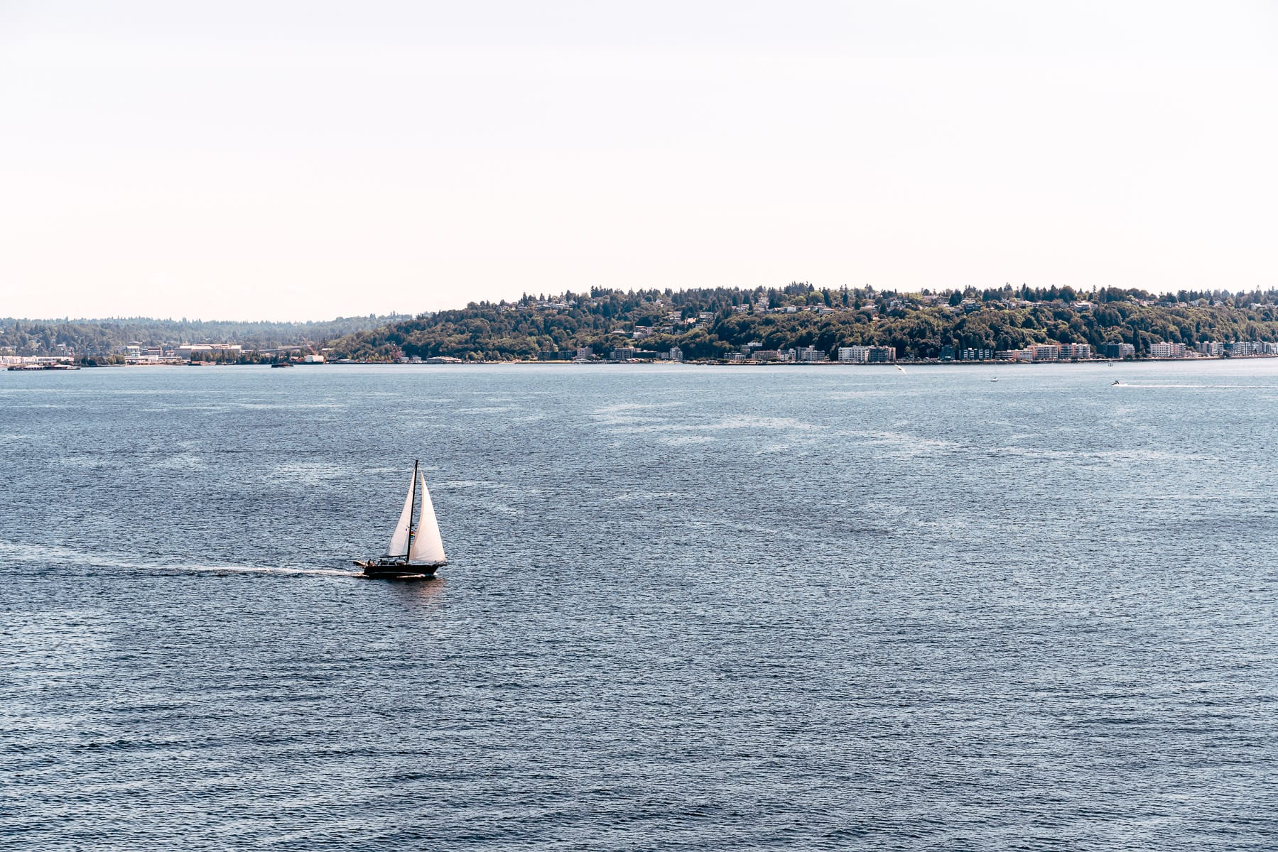 A sailboat plies the waters of the Puget Sound in the Salish Sea near Seattle, Washington.