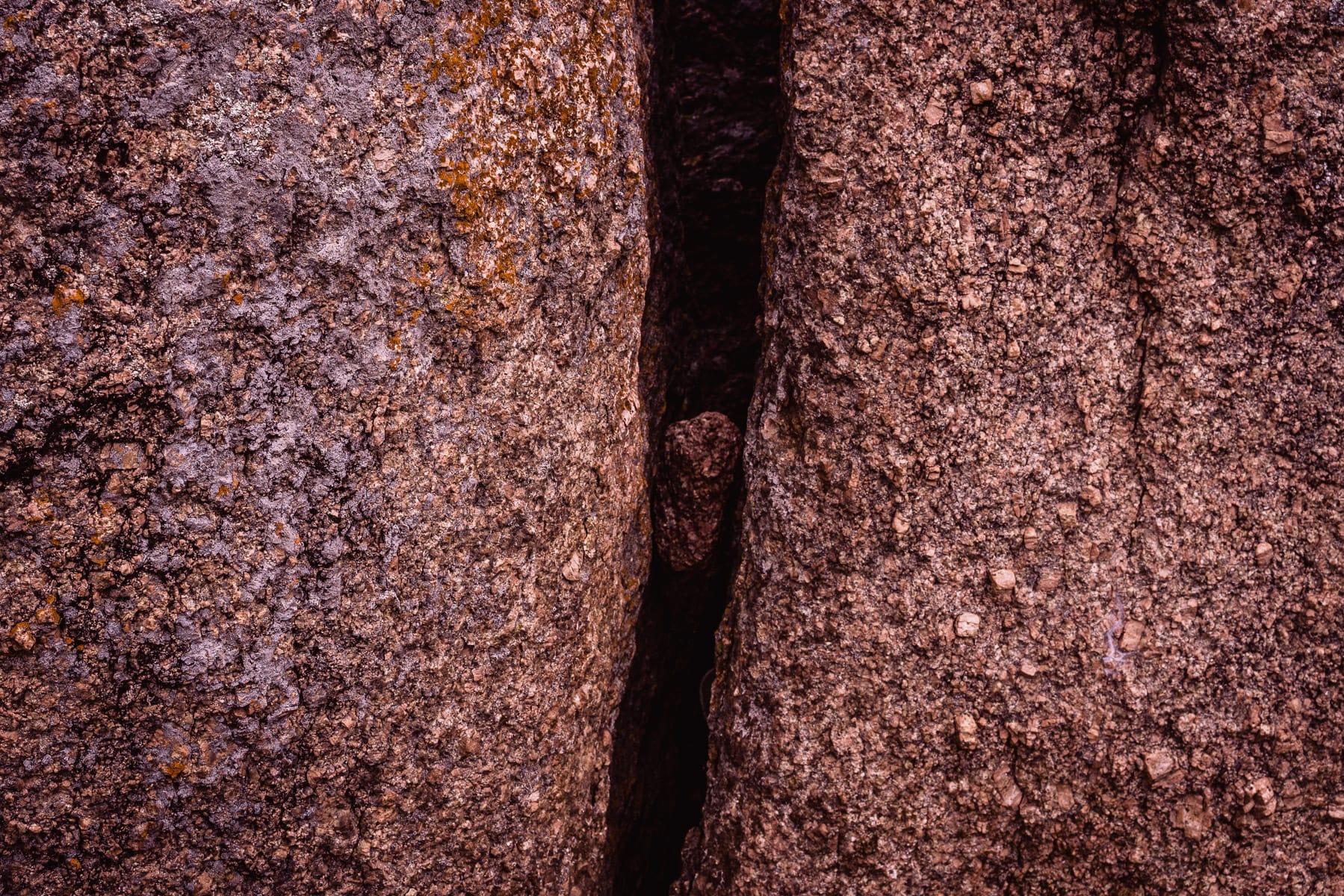 A rock trapped in a chasm between two larger rocks at Enchanted Rock State Natural Area, Texas.
