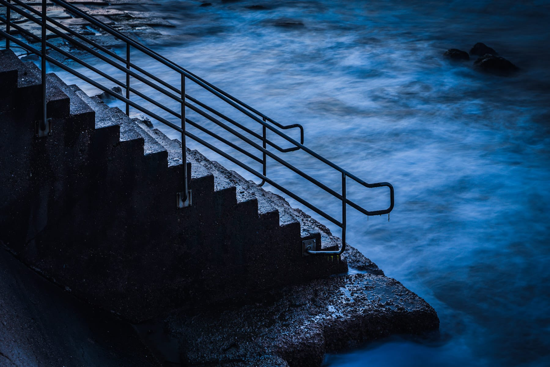 Stairs on the Galveston, Texas, Seawall lead to the swirling waters of the Gulf of Mexico.