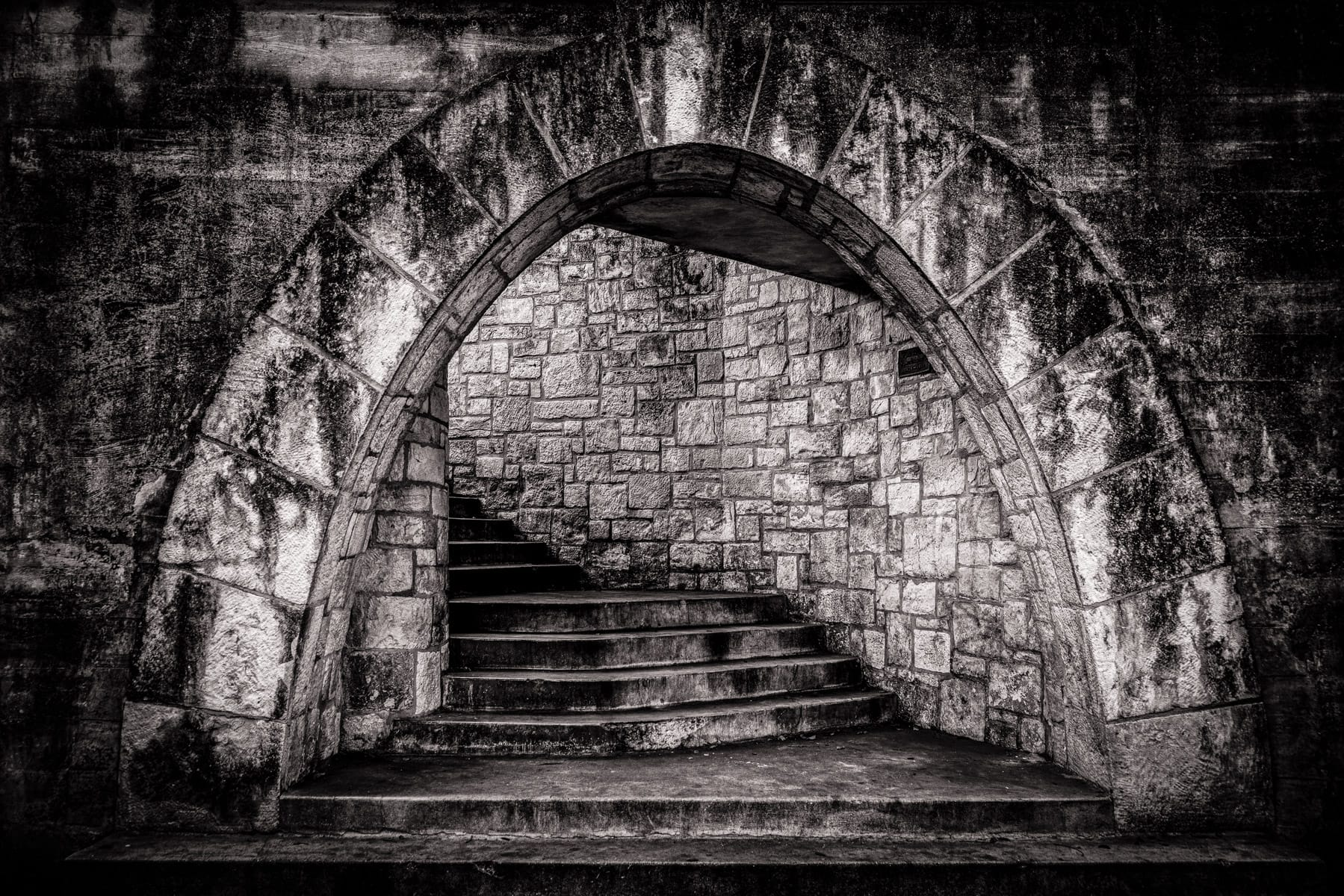 A stairwell is framed by a stone arch along the historic San Antonio Riverwalk, Texas.