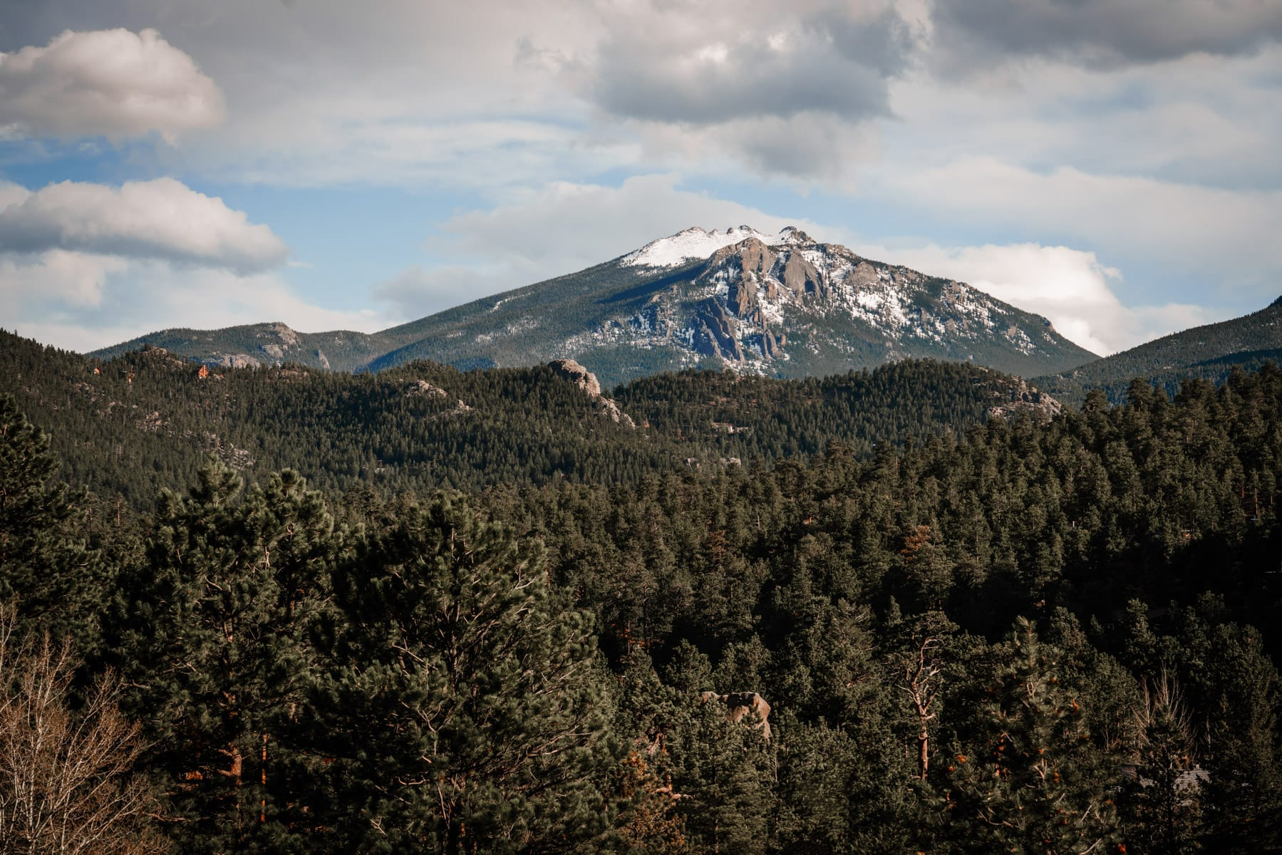 A rugged mountain rises above the evergreen forest at Colorado's Rocky Mountain National Park.