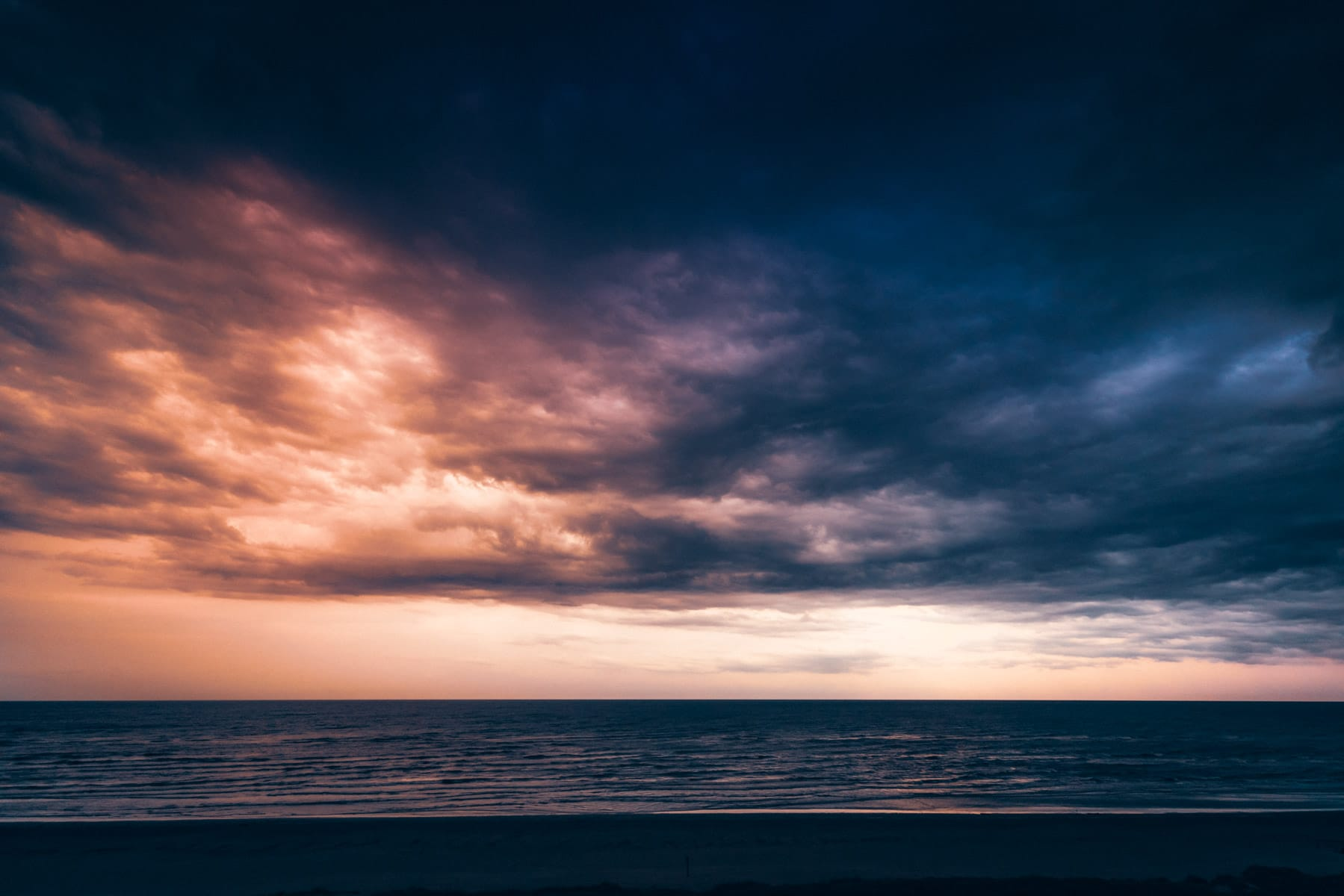 The sun rises over the Gulf of Mexico along the Galveston, Texas, beeach.
