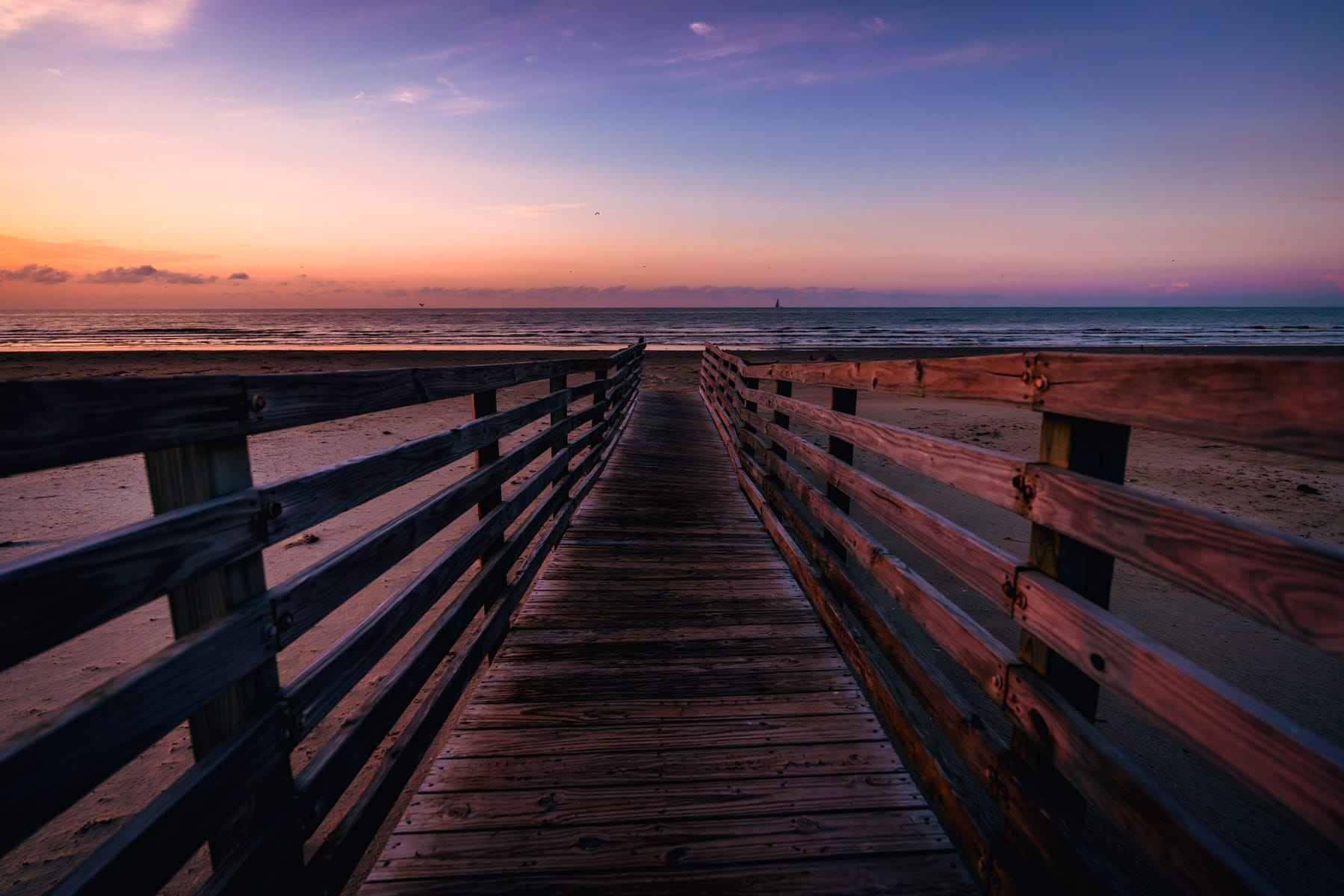 A wooden walkway leads to the Gulf of Mexico beach on Galveston Island, Texas.